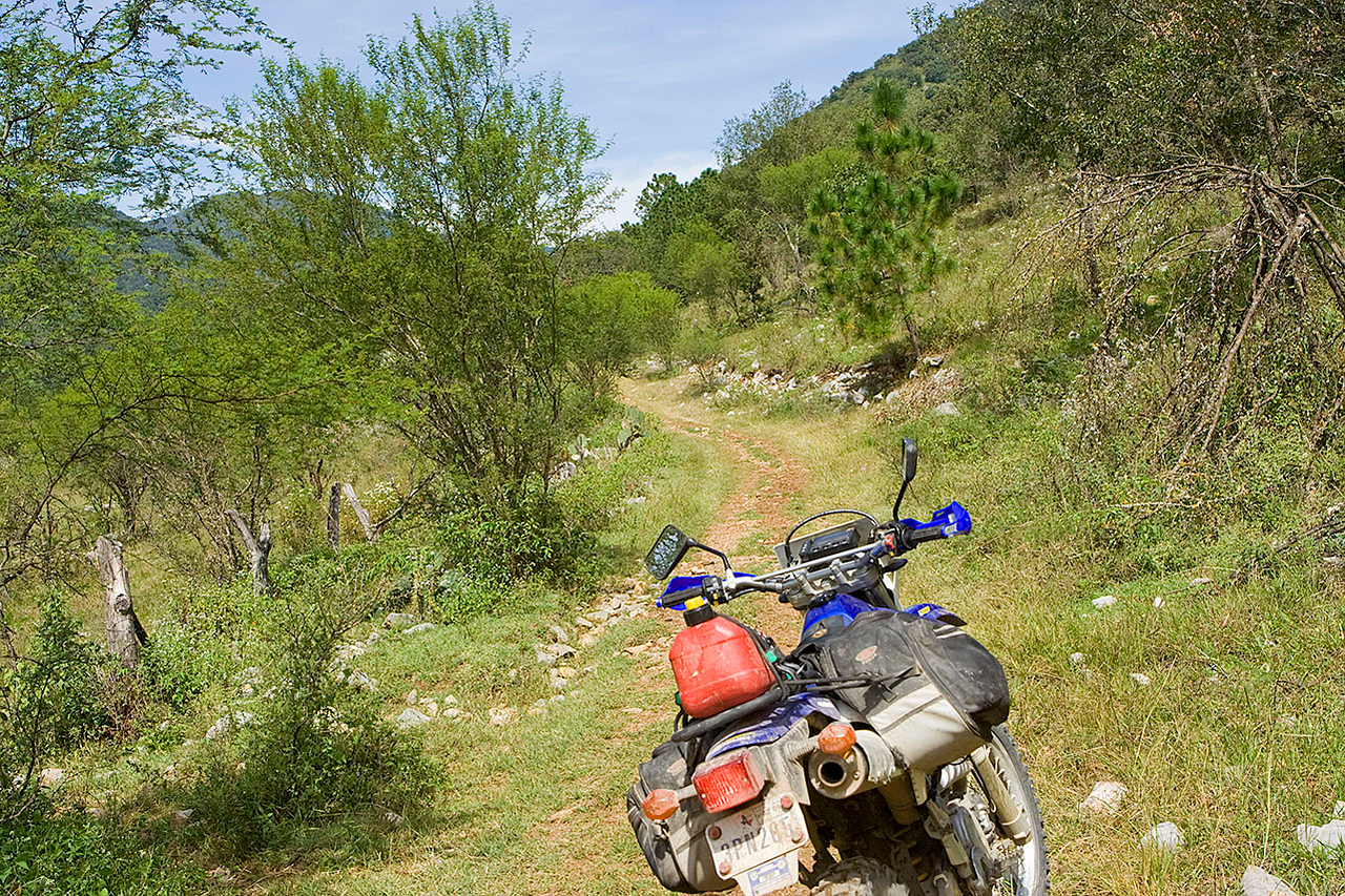 Cow trail<br /> Soon, there were no more gates or fences to close, and our cow trail gave way to a steep gnarly uphill scramble. Finally we crested a pass of some sort. By now we realized that if one of our bikes were to break down out here, the only way we were getting it out was in pieces, on horseback. <br /> <br /> And now we had the formidable task of descending the other side of the pass on an equally gnarly wash. No one took pictures up there, as far as I know. We were all too busy trying not to worry.<br /> <br /> Well, at least we were over the pass, I reasoned. It was all down hill from here........<br /> Right?<br /> Well, nooooot exactly.