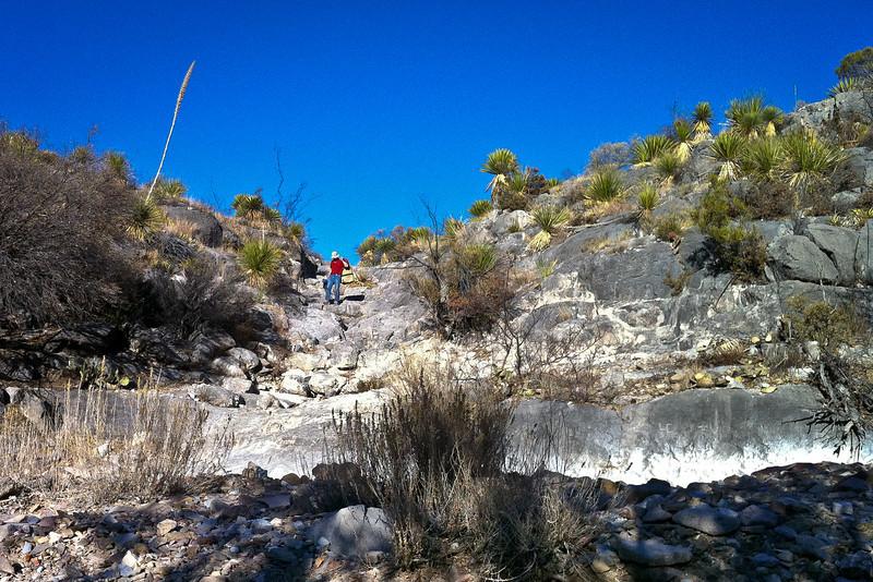 John carrying gear down the boulder chute.