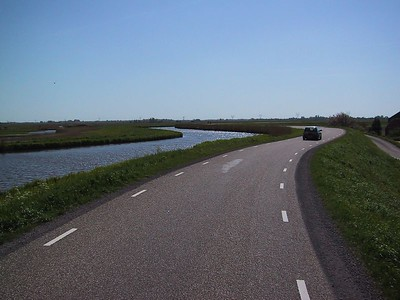 A dikeroad twisting along the water. Notice that the water on the left is higher than the land down to the right.