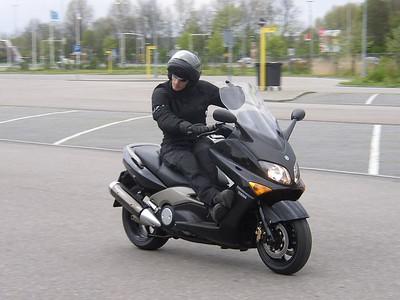 Ja, Emile's T-max. De GS is niet meer, deze gloednieuwe 2004 Yamaha XP500 T-max is het allernieuwste wapen. Tot dusver zijn alle proeven met het grootste gemak doorstaan. Ook het rijden met de benen aan 1 kant blijkt niet al te uitdagend te zijn ;-).
