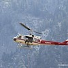 The rescue copter hovers while a rescue climber clips on to the line below.