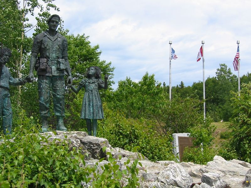 The statue mentioned in the description relative to the plaque and flags