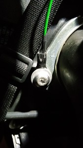 The coated cables are attached to air duct flange bolts near the steering head. The strap pictured was included with the bag but will no longer be used.