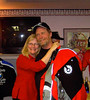 Joe Skaggs gets a hug from Voni after winning the auctioned Belstaff jacket donated by Bud Meade.