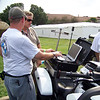 Rob shows his computer setup to an onlooker.  The computer is the one that attaches to the top of his tank bag.  It's a touch screen Toughbook with a waterproof keyboard.  On the screen at the time was Internet weather radar.