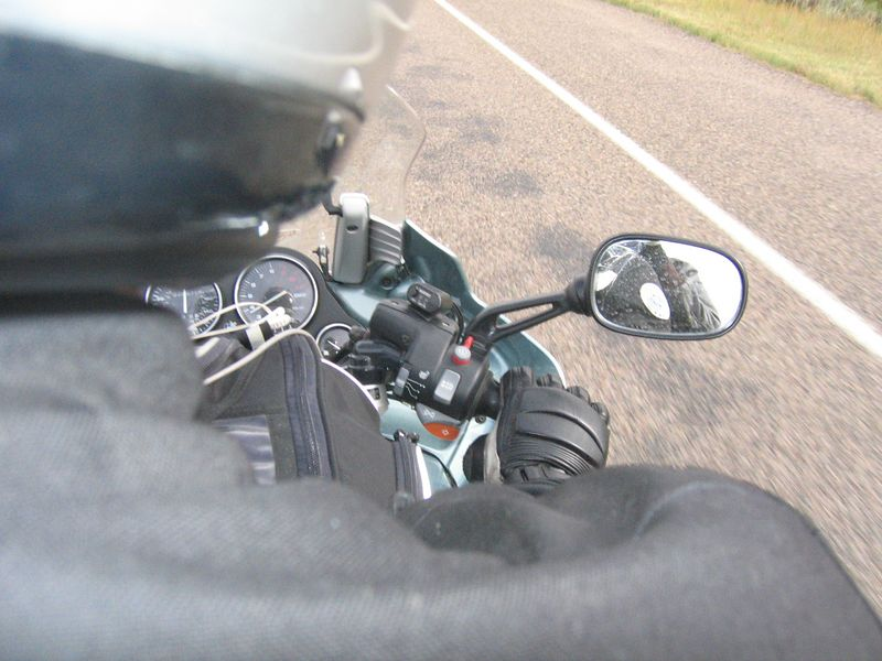 "Maria's view from the pillion seat.  As you can see, we were just putting along.  Unfortunately, the Wyoming State Patrol seemed to be targeting motocycles on Saturday, and I was hit with Instant-On even though I was pacing a truck.  My ""rabbit"" was ignored, and the instant-on deliberatly targeted at me, even though we were travelling at the same speed.  <br /> <br /> The officer eventually confided that he preferred to target the last vehicle in a group, so that he didn't have to chase as far as going after the first one."