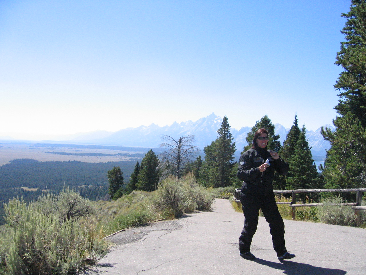 Deb Sauer takes a picture, with the Grand Tetons looming in the background.