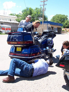 Taking a break to deal with a slow leaking rear tire on a Goldwing. The owner, Bertram, is on the ground. Dan, with the pipe, is only supervising.