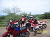 "It was monsoon season in Tucson, but since we hadn't been able to coordinate schedules for a long time, we decided to ride rain or shine. The overcast sky helped keep the temperatures down all day. We met at the gate at the end of  Wilmot, south of Sahurita Rd. Here are Jim, Troy, and Craig near the start of the ride. As you can see, Troy is especially excited to be out. He demonstrated a master's ability in power sliding around corners on the ride to this point. This was the last photo with the bikes still relatively clean... except for Craig whose bike was filthy before we started. When we asked Craig why he hadn't washed it he replied, ""Why bother?"""