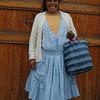 Una mujer arequipena, con sus atuendos,  vendedora de munecas que ella misma confecciona imitando el vestuario de las mujeres de su region, guarda en su bolsa varias de ellas hasta darle el ultimo arreglo.  Posa para la foto contenta de haberla seleccionada y agradece.  Gracias senora.