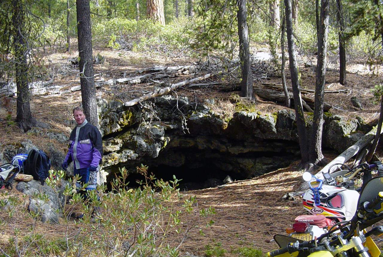 "Our first goal before trying to make the pass on Paulina Peak was to try and find ""Surveyors Ice Cave"".  This was the first time that I used my computer to locate something, create a way point, then transfer that waypoint to the GPS, then, without an actual <b>route</b> programed in, try to find that location.  Pretty fun..  I can see what the fuss about <a href=""http://www.geocaching.com/"">Geocaching</a> is all about now..   I also discovered that there are some limitations to the little GPS on the handlebars..  Imagine a destination so far away, that when you have it and you on the screen, all the roads dissapear from the display.   When you zoom in enough to see all the roads in the area, you can't really see where they lead.  At least not without fumbling around with the thing at every intersection in thick gloves.  If you go back and look at the map, you can see the results.  I was trying to aim for aproaching the cave from the south, but all the roads dead ended just short of the cave.  We ended up bearing <B>WAY</b> more to the west than I'd indended, and missed a short section of road that would have taken us straight there.  Of course, ""straight there"" wasn't exactly the goal to begin with, so no big deal, I guess.. <br> Getting back to the cave part, vs. how we fumbled our way there, this is a 210 foot tunnel that leads back into the mountain.  Supposedly.  It was full of ice with about 6 inces of <B>cold</b> water on top of that.  We made it down into an intro cavern about 10-12 feet across, and a small channel leading to another cavern that looked quite large.  Problem was, you'd have to lay down in 6"" of ice water to skinny through.  Not today, thanks.  It's bad enough that my boots are now full of ice water..  ;-)<br>We had a nice lunch break here..."