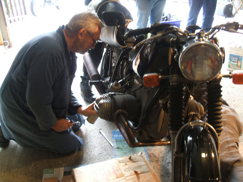 Dale applying muffler fluid to Bryan's bike.