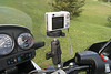 A lightweight Casio EX-Z110 digital camera mounted in position. An Olympus C-5060 WZ is also used in its place.<br /> <br /> This set-up places the camera behind the OEM windscreen and out of the direct blast of bugs (as well as rain provided the camera is waterproof) while riding.<br /> <br /> This set-up is handy in that the camera can quickly be taken off its mount and placed back in a snap without having to open up a tank bag or having to search through pockets in your riding gear.