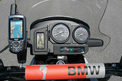 "The GARMIN GPSmap 60Cx as viewed from the seated position.  Note the Garmin lanyard that I've looped around the stalk of the mirror to act as a tether.  Although not a concern because the 60Cx is waterproof, the positioning places the unit behind the windscreen out of the direct blast of rain while riding.  Positioning also places the unit close to the rider for better viewing and access to the GPS controls. More importantly, positioning doesn't obstruct the view of the Rider Information Display (RID) or the instruments. The reason why I chose not to go with the ""speedometer mount"" method was that its positioning of the GPS clearly obstructed the view of either the RID or the instruments, depending on the GPS in use. Cost? Under $10 or € 6.  I now have a modified RAM-B-236 ball mounted on a modified BMW threaded bushing on the right handguard as well. It is used to mount a digital camera."