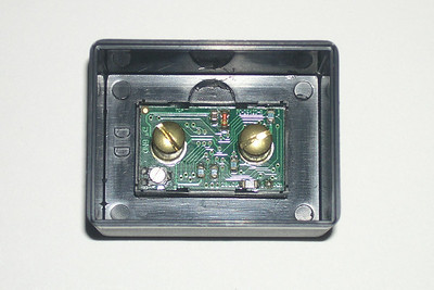 "The back view of the Datel digital panel meter mounted in the BUD potting box.   The two brass screws are connected to Ground (marked on the board as GND) and Positive. These should be connected directly to the battery terminals with a fuse as close as possible to the battery in the Positive line. A relay to switch the meter out of the circuit when the ignition is off is not required as the meter only draws 2 mA and any healthy battery will be able to handle that current draw over a few weeks.  I used RG-174 A/U coaxial cable to wire the meter to the battery. The 0.1"" diameter coaxial cable is round in cross section and the braided wire acts as a barrier in case the cable should chafe. The center conductor is positive, and the braid for obvious reasons, is negative. I also put high quality rubberized heat shrink over the coaxial cable to further protect it.  The silver colored screw at the bottom left is used to adjust the voltage so that the meter reads accurately in the 12 to 14Vdc range. The meter was off by 0.1 to 0.2V in this range."