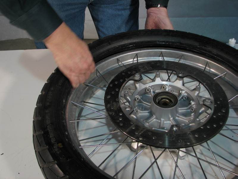 Opposite the side where you lubricated the INSIDE of the tire bead, slip the tire over the rim and fit it into the CAVITY