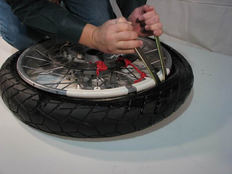 Slip tire iron #2 into the gap between tire and rim.  Hook the upturned spoon onto the edge of the tire bead