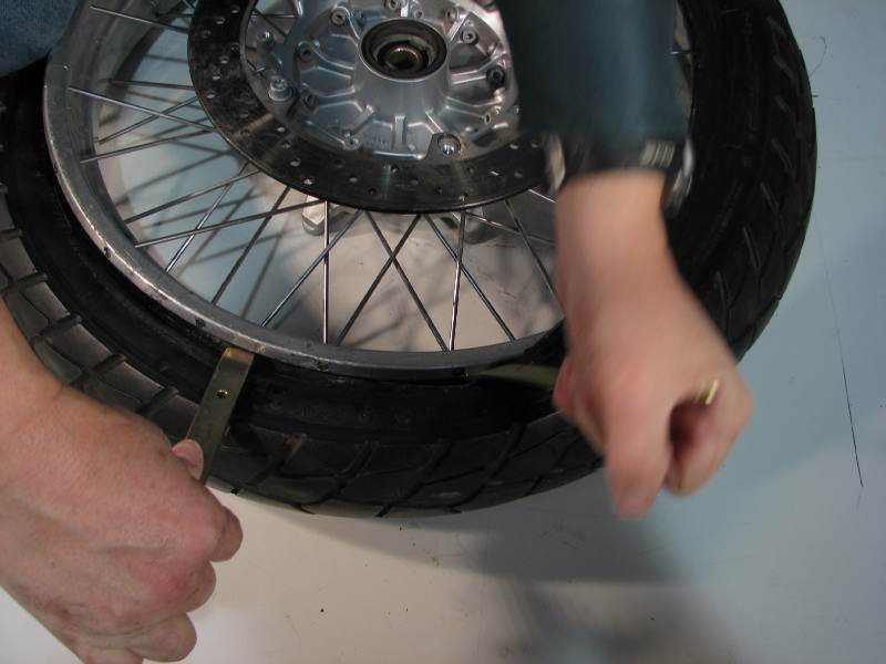 A few inches further up the tire, insert a 3rd iron and rotate it so that the tire slips over the rim