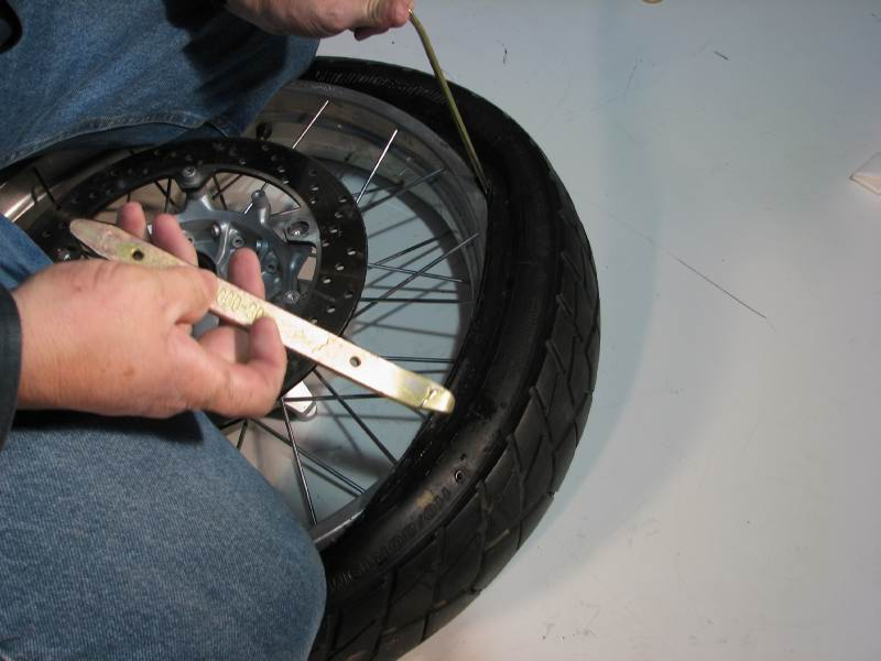 I'm almost over the rim.  A single tire iron is between the tire and rim, held by my left hand.
