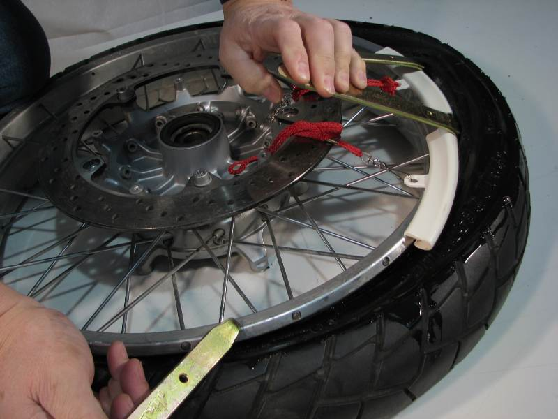 Remove iron #2, and move it to the right of the iron #3  Press #2 down and continue working around the tire.  Iron #1 remains in place to prevent the bead from slipping back down