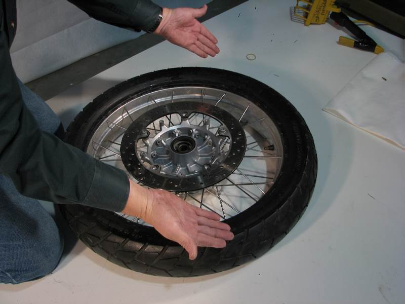 I did such a good job of lubricating the tire bead, that the tire popped right onto the rim without the need for any tools !!!  But in some cases you may need to use a tire iron to help the 1st bead over the rim  If you're struggling with this process, make sure the bead closest to your knees is inside the CAVITY of the rim