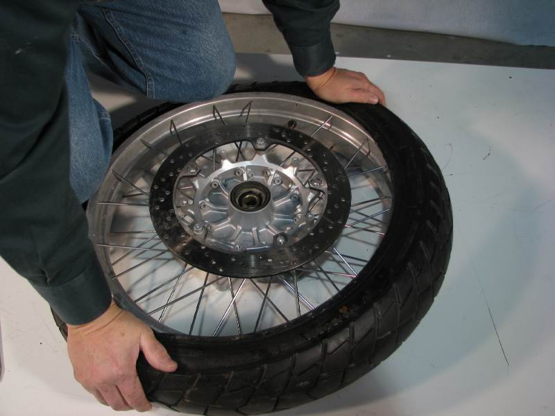Kneel on the tire, crushing it so that the bead will fit into the CAVITY  With your hands, work the bead over the tire, pushing it onto the rim. Go as far as you can, equally, working away from your knees