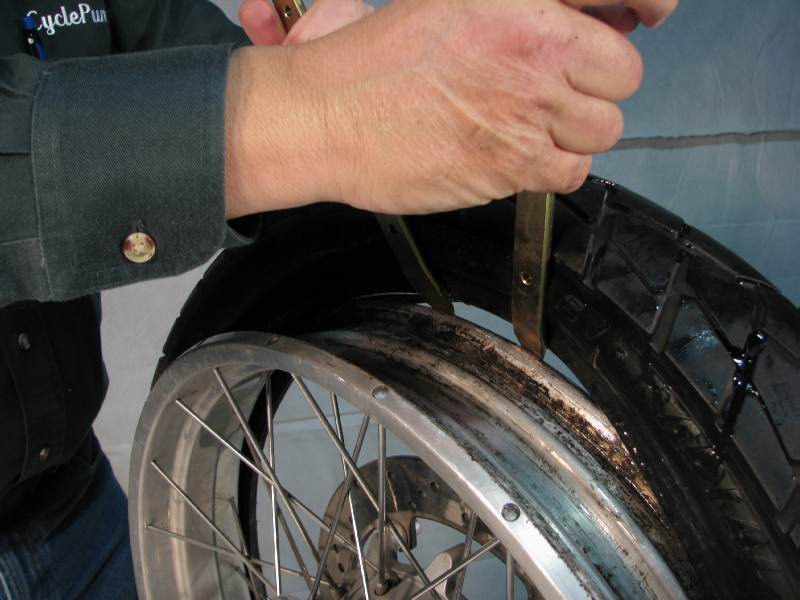Slowly press the rim down, as you rotate the spoons over the top of the tire