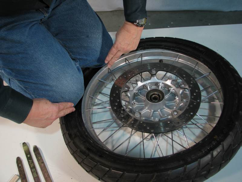 Kneel on the tire, crushing it so that the bead will fit into the CAVITY