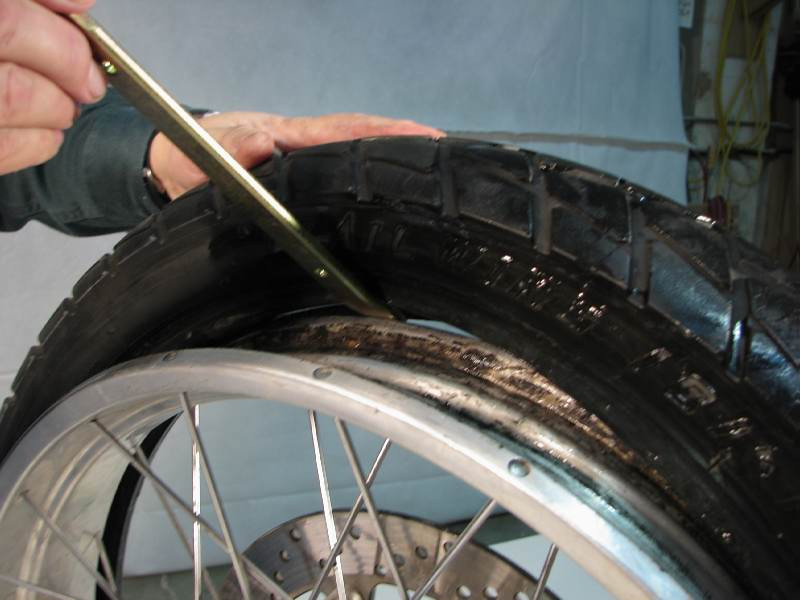 Insert a tire iron between the rim and the tire