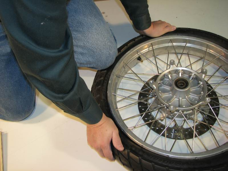 Your knee is also helpful to push the tire away from the rim.  When doing this I'm being careful that I don't damage the disc.    In some cases you may need to put small blocks under the rim to keep the disc off the ground