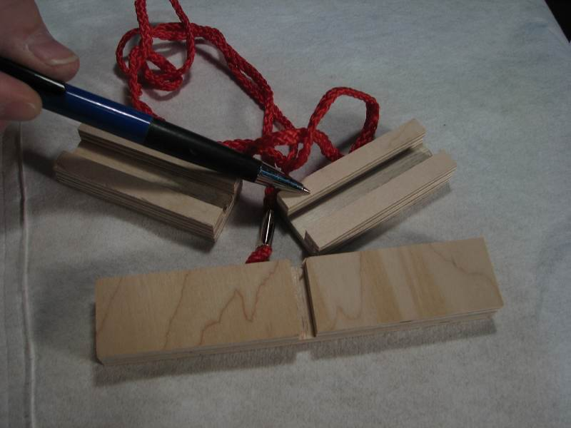 The small wood blocks have slots in them that fit the inside edge of the CORNER.  