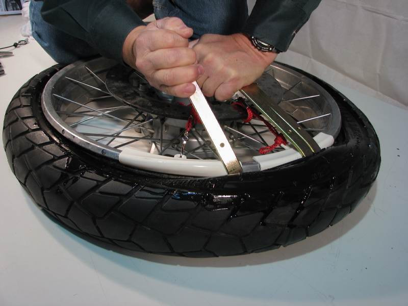 Press tire irons #1 and #2 down.  Slip tire iron #3 into the gap a few inches away and press it down.    The tire is starting to slip over the edge of the rim and the rim protectors