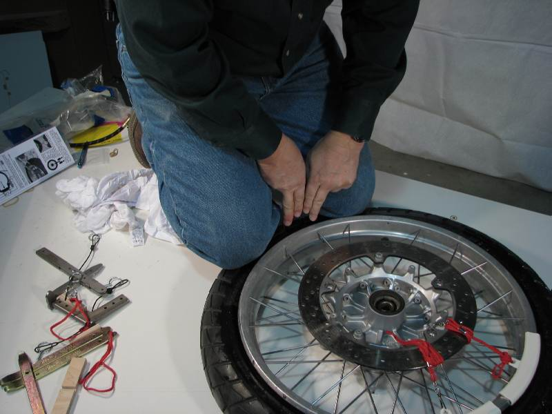Again I'm kneeling on the tire, compressing it so that it will move into the rim CAVITY