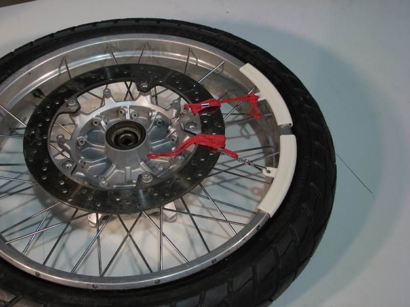 Plastic rim protectors keep the tire irons from marring the rim.  They snap on the rim and are held in place by friction, and also by the lanyard tied to a spoke or the rotor.