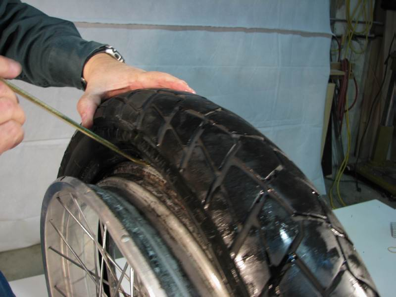 ****** At the bottom of the the tire, make sure it's resting in the rim CAVITY. ***** This gives maximum clearance at the top of the tire, where you'll be working.  Insert a tire iron between the rim and the tire