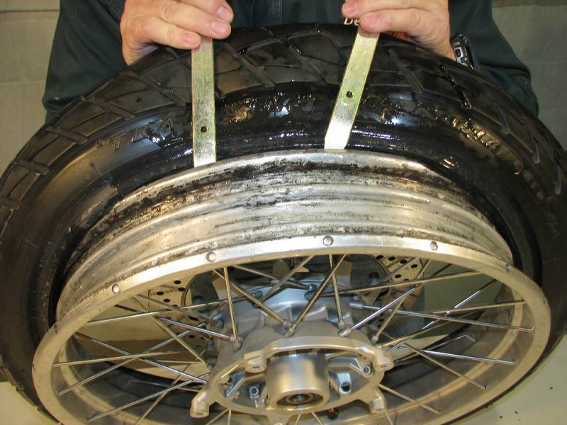 I've spun the tire aound, now I'm on the side with the rubber tire  I continue to press down on the tire irons