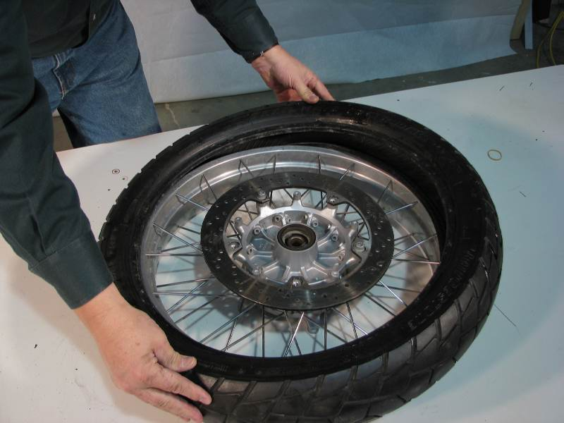 Making sure my rotations are in sync...  I lay the tire over the rim.  Press down the tire nearest you, make sure the bead fits into the CAVITY of the rim