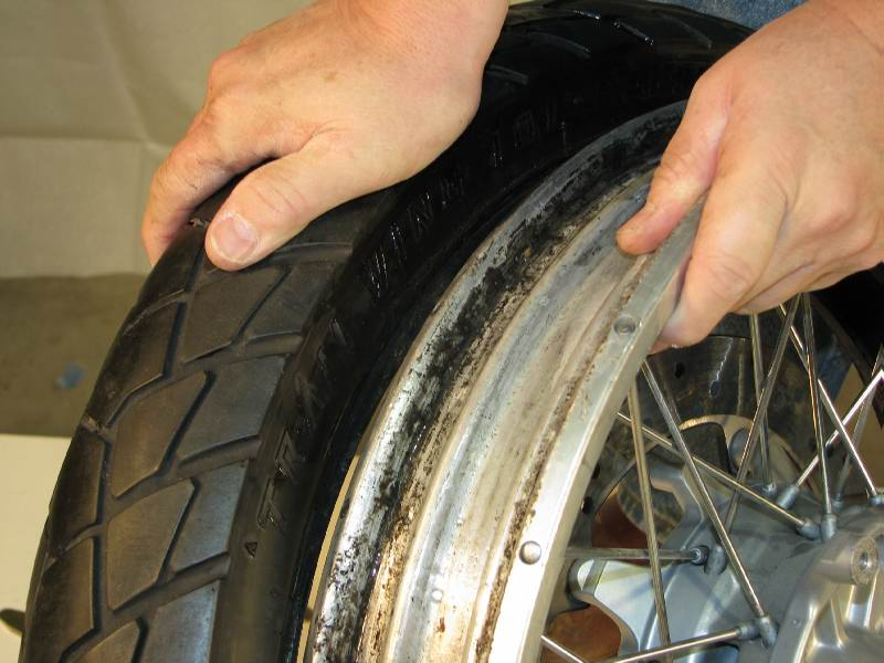 Press downward firmly on the top of the tire, and push it away from the rim