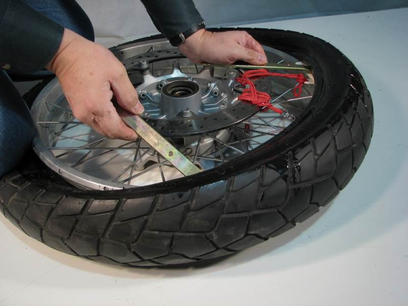 I continue to work around the tire.  Remember that Iron #1 remains in place, and irons #2 and #3 leapfrog to the right as they work the tire off the rim