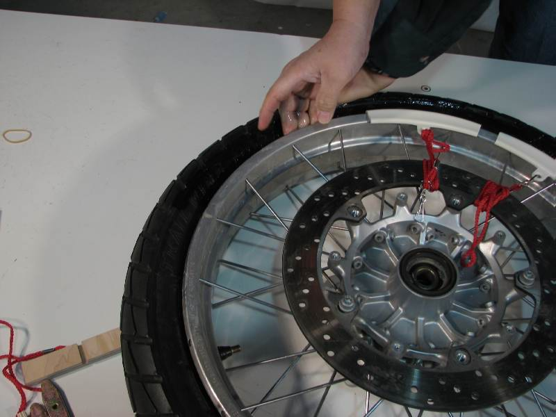 I compress the tire with my left hand, and use my right fingers to distribute the BeadGoop