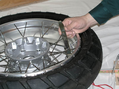 15.  The vertical tire iron is fitted up thru a wide spot in the spokes.