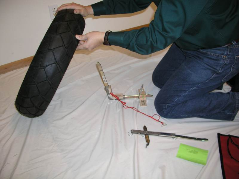 13.  Lift the wheel and lower it onto the vertical tire iron.