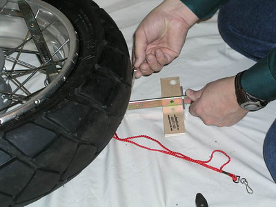 17.  Pull the BeadBrakR toward you, so the vertical tire iron and plywood blocks are  TIGHT against the inside of the rim.  Then slide the Lock Bar TIGHT up against the tire.  This prevents the device from moving in relation to the tire/wheel assembly.