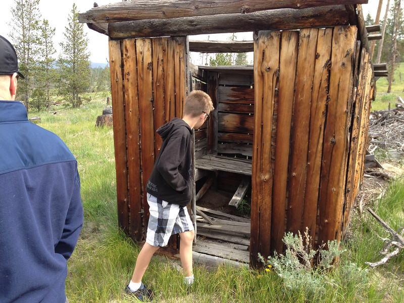 6/24 - My nephew, Nate, checking out the outhouse leftover from the logging camp. The boards with the circular bits were laying in the debris on the ground. Neat stuff, lol.