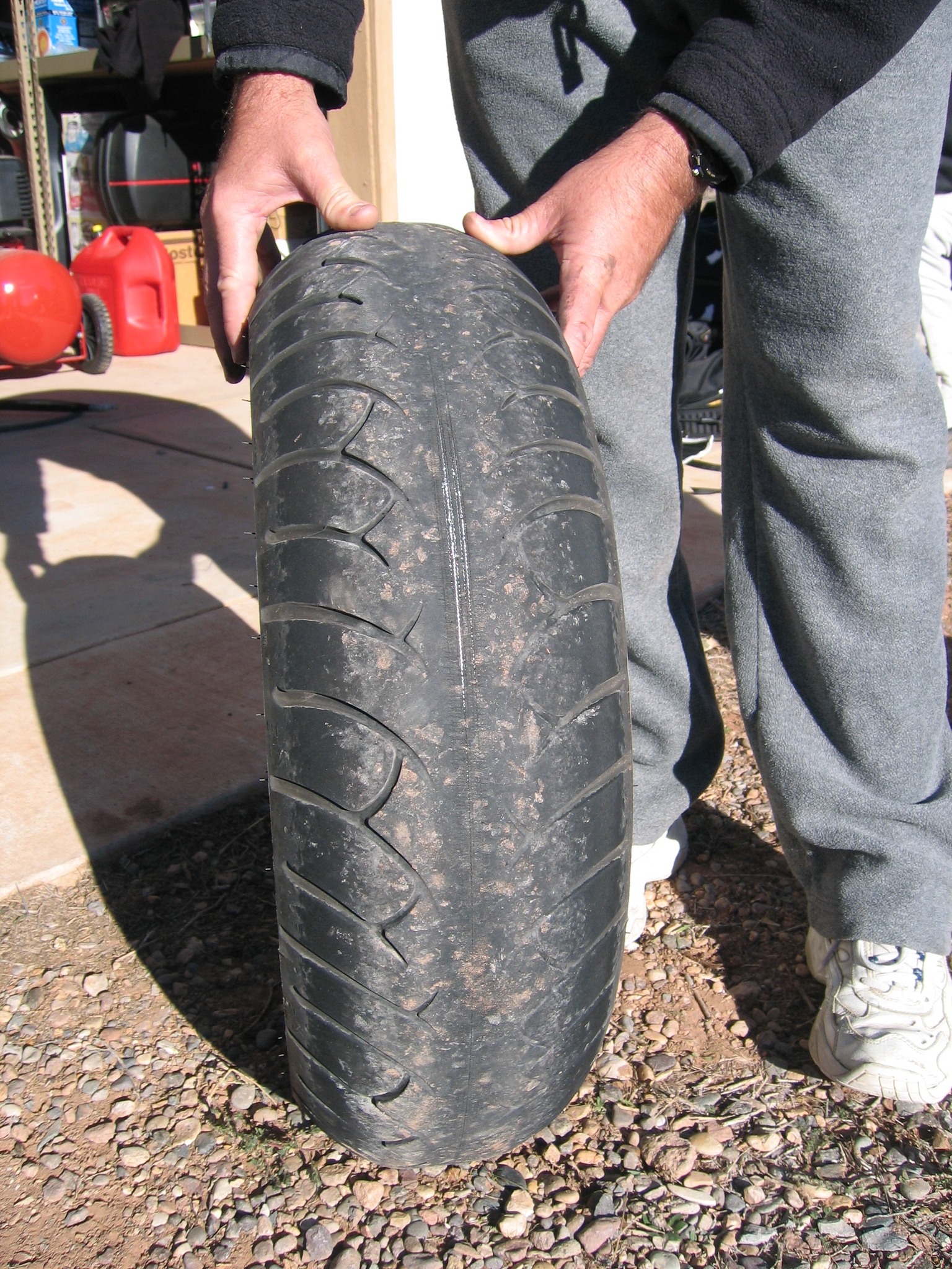 "On return from the Lake Powell loop, Thor found the infamous shiny sliver ""wear bars"" on his Z6 tire.<br /> <br /> On Sunday morning with Bob Palin's generosity and a cast of thousands led by Jamie, Thor had a servicable tire on his bike for the trip home."