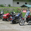 The parking lot at Wheels Through Time: Honda Valkyrie, Craftsman lawnmower, Harley, Kawasaki Vulcan.