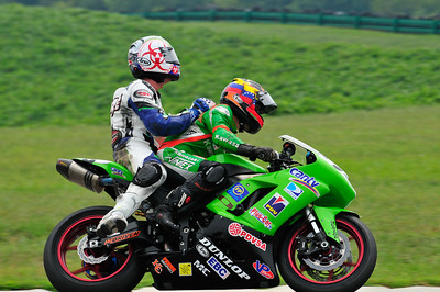 Amantini gives a fallen rider a ride back at the end of the Supersport race