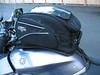 The curved profile of the bag fits the tank shape.  The foam pad attached to the bag protects the paint and keeps the bag from slipping around.  Nelson Rigg provides an exceptional value for under 90 bucks with this  luggage.  Shoulder straps are included to convert it into a backpack.  They unclip and store inside.