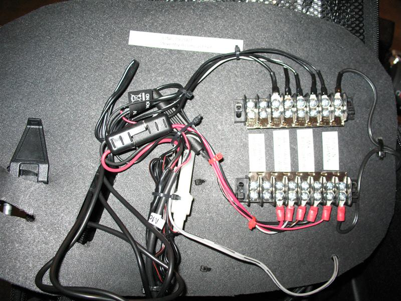 The underside of the Circuit Board.  Here is the 12 volt power coming in from the tankbag pigtail SAE connector on the right.<br /> Fuse holders come inline with the Garmin and Escort cords.  Tie wraps are used to anchor the barrier strips, battery charger and various cables.