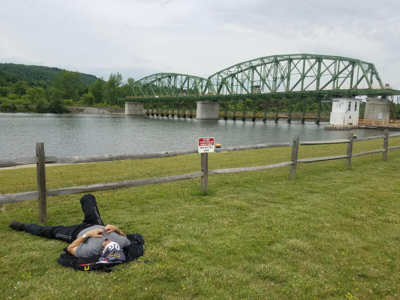 rider sleeping on grass by Erie Canal